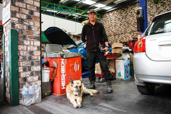 A man in his mechanics workshop with his dog