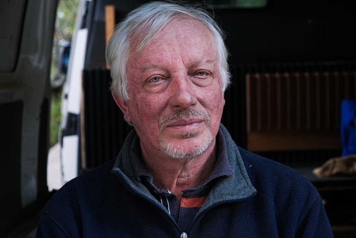 Profile shot of Simon Crosbie, staring into the camera as he sat in the back of his van.