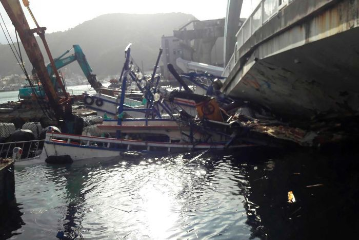 Crushed fishing boats lie under the collapsed bridge