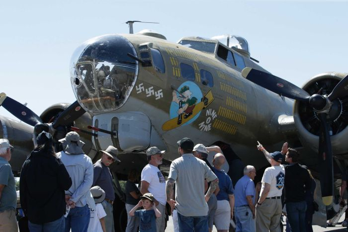 Plane fans crowd around a B-17 vintage WWII era Flying Fortress, painted olive green and with anti Nazi imagery