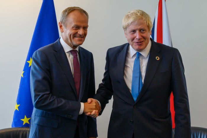 Donald Tusk shakes hands with Boris Johnson in front of EU and British flags.
