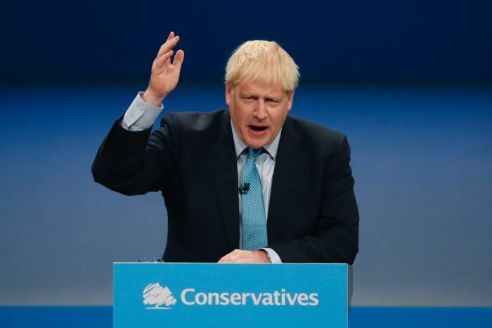 Britain's Prime Minister Boris Johnson holds his hand to the arm as he speaks from a podium.