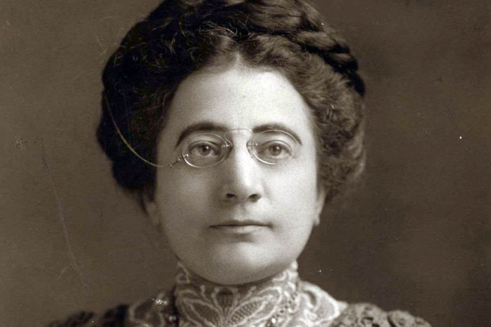 A woman with glasses perched on her nose sits for a black a white portrait, c. 1912.