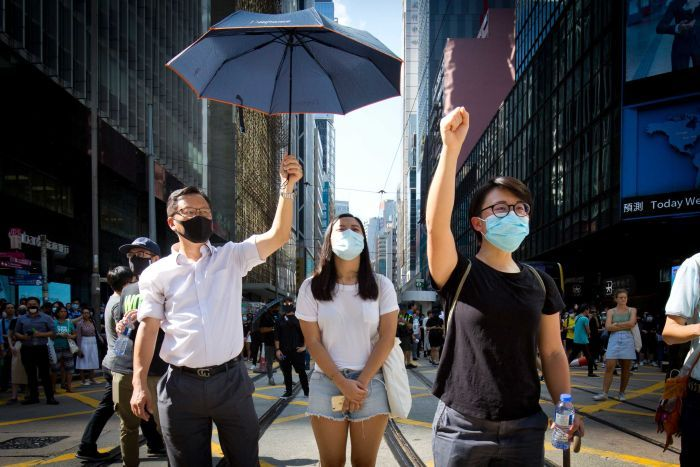 Three protesters stand close to the camera with masks on, one holding an umbrella.