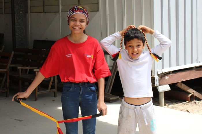A girl wearing a headscarf smiles and stands next to a younger boy holding up a plait in red, white and black colours.