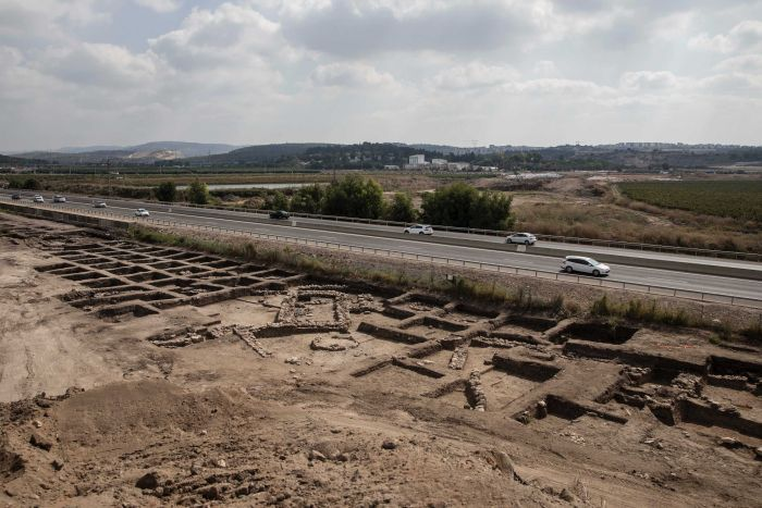 A patch of dirt next to a highway is excavated and shows evidence of what looks to be an ancient city.