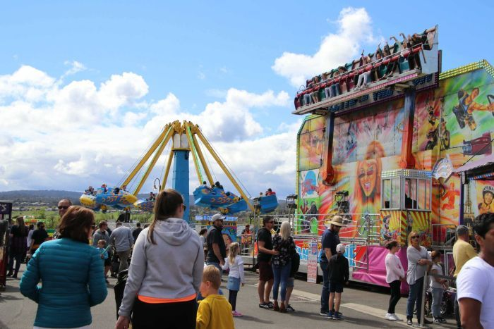 Spectators walk past carnival rides at an agricultural show