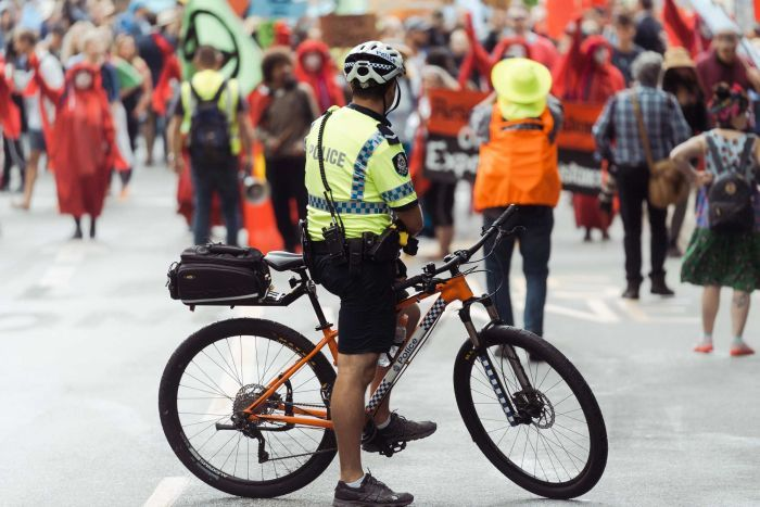A police officer on a bike looks at a large group of protesters.
