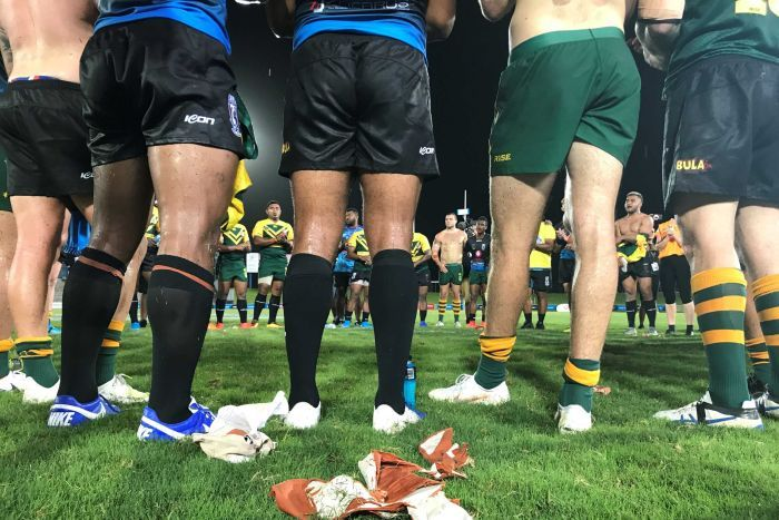 Photo shows men standing around in a circle after a rugby match.