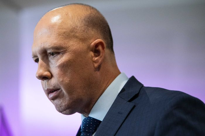 A close up of Home Affairs Minister Peter Dutton looking down