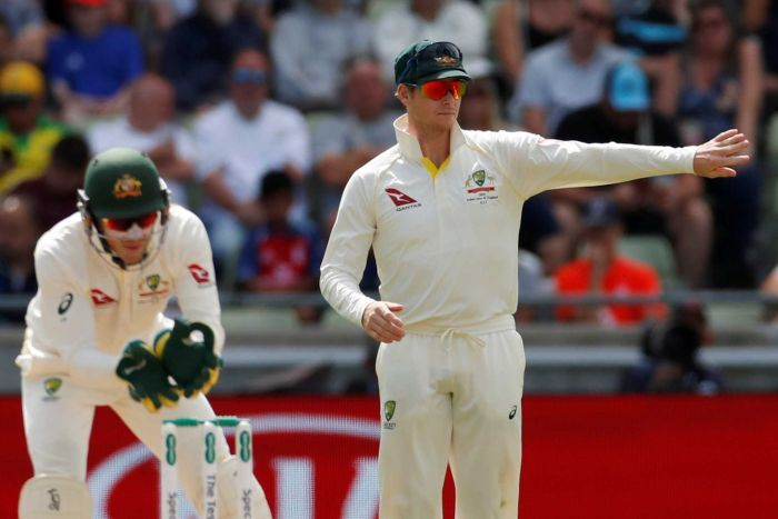 Steve Smith directs fielders while Tim Paine mimes wicketkeeping during a Test match.
