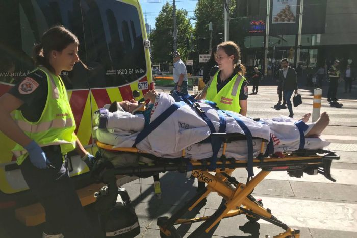 A 23-year-old woman is strapped to a stretcher and is about to be loaded into an ambulance.