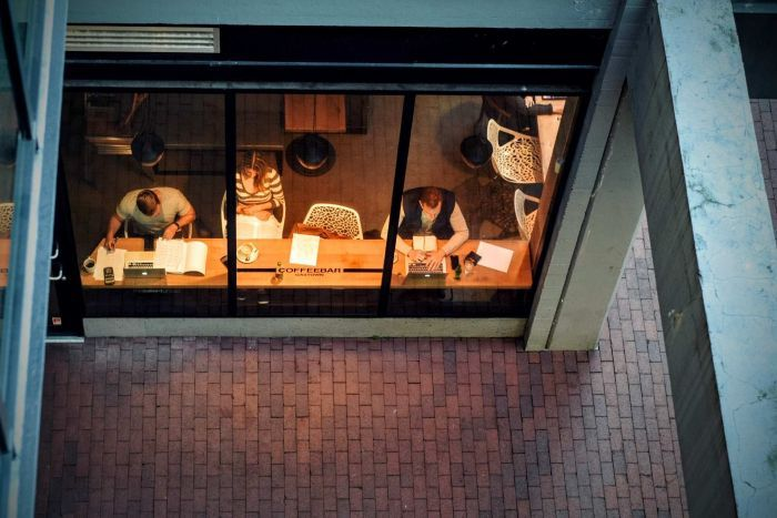 Three people work at a cafe