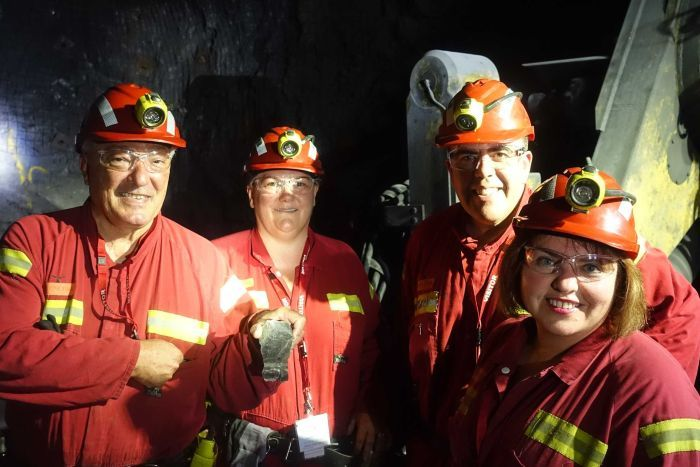 Four politicians in hardhats and hi-vis jumpsuits smile underground in a mine