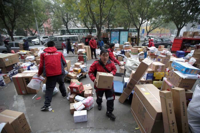 Deliverymen wearing red work among parcels beside a road in Beijing, China.
