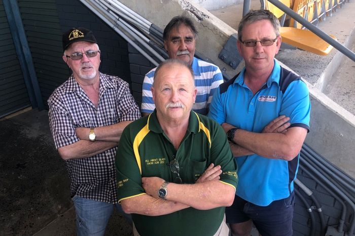Four greyhound trainers stand with their arms crossed, not looking too happy