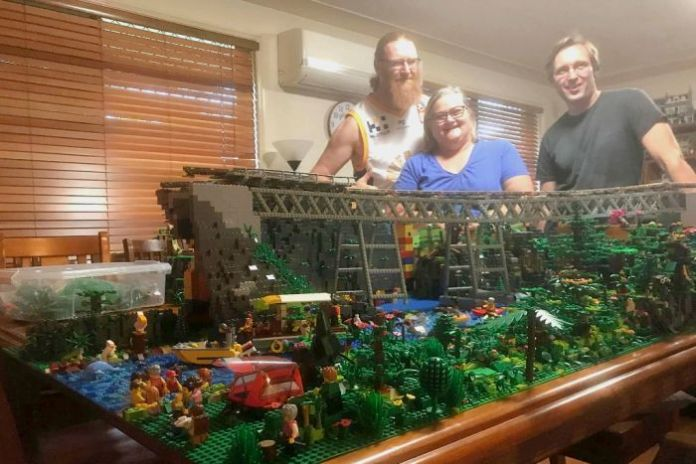 Three people standing behind a large Lego display of a railway bridge surrounded by rainforest.