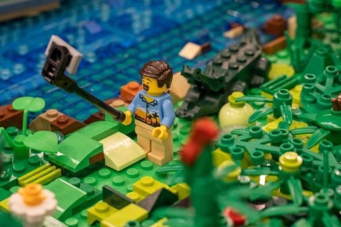The Lego statuette in a tropical shirt takes a selfie with a crocodile behind it.