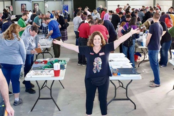 The woman stands with open arms in front of dozens of people scanning boxes of Lego pieces.