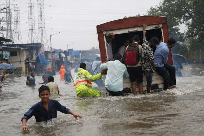A group of people ride on the back of a truck in floodwaters in India