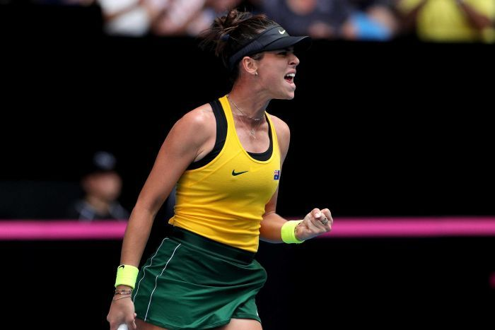 A tennis player punches the air after winning a game.