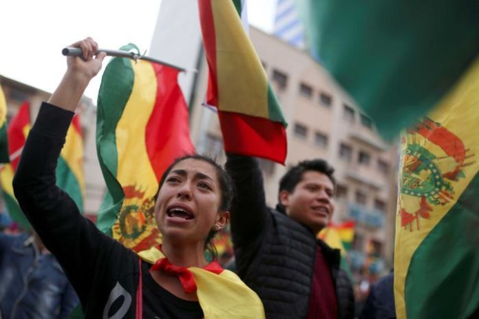 A woman with a painful expression stands in a crowd of demonstrators waving Bolivian flags.