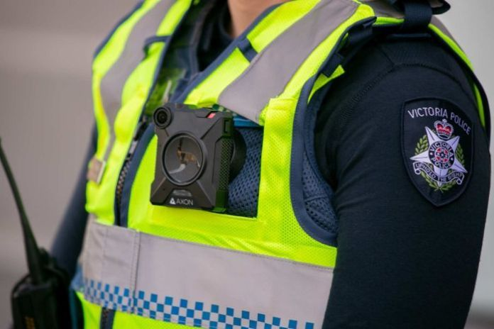 A square camera carried on the yellow vest of an unidentified police officer from Victoria.