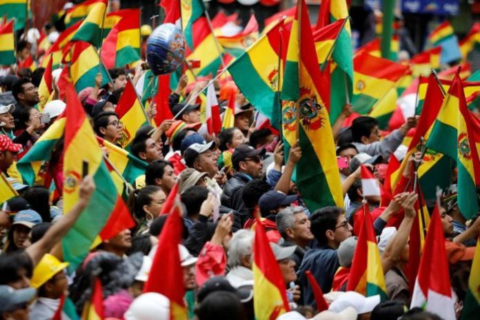 A large crowd waves Bolivian flags in the air.