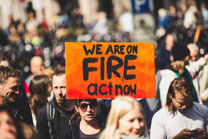 Woman holding a sign that signs 'we are on fire act now' at a rally.