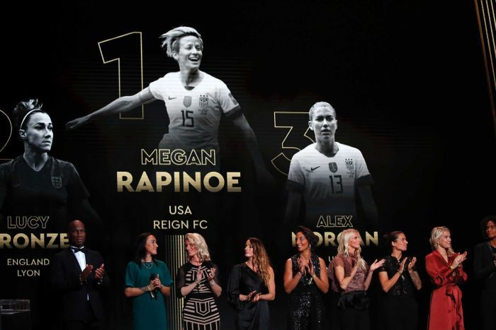 Podium of women's Ballon d'Or winner projected over a stage, with Rapinoe first, Lucy Bronze second and Alex Morgan third.