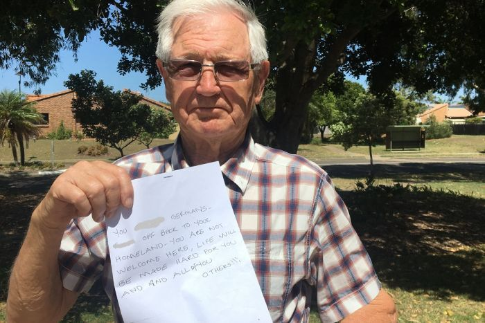 An older man holds up a letter