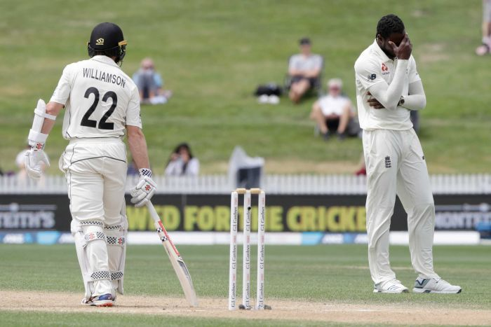 A bowler has his hand over his face in frustration, as the batsman looks on after being dropped.