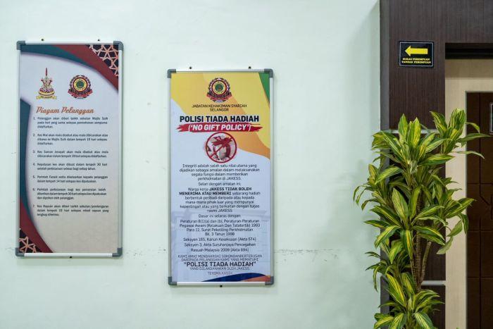 """Signs inside a sharia high court in Malaysia, written in Malaysian, say """"no gift policy""""."""