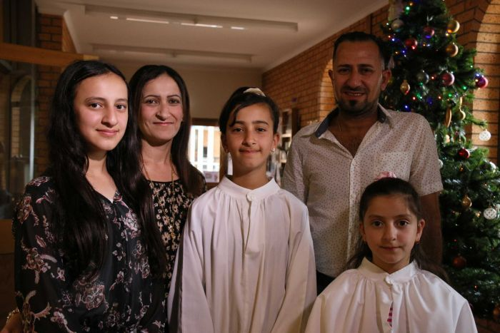 Nashwan Matloob and his family stand together looking at the camera.