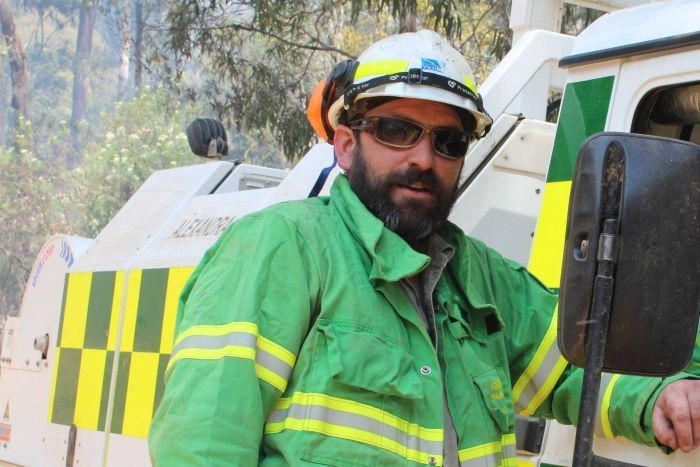 Mat Kavanagh, dressed in green firefighting gear, stands next to a truck in the bush.