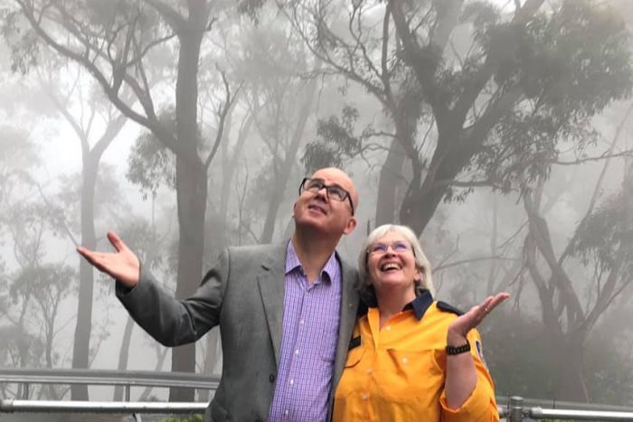 man and woman looking up and smiling under rain