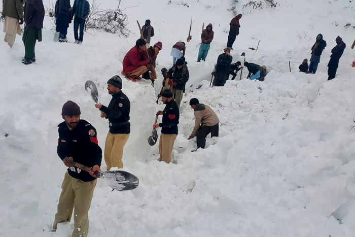 People with shovels dig in the snow to find avalanche victims.