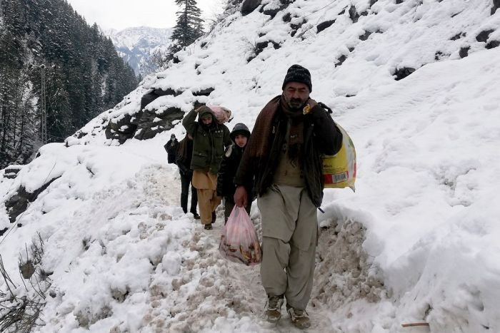 The Kashmir villager walks on a snowy road with bags in his hands.