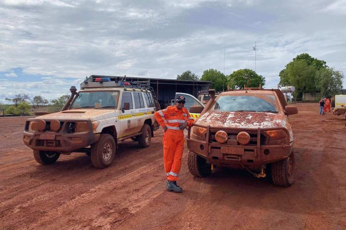 An SES volunteer poses with two very dirty four wheel drive vehicles