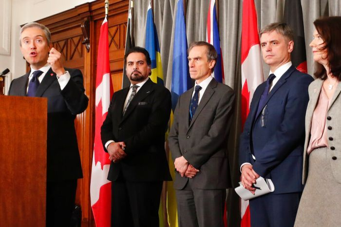 A line of officials wear are in formal workwear as they stand in front of national flags in an ornate office.