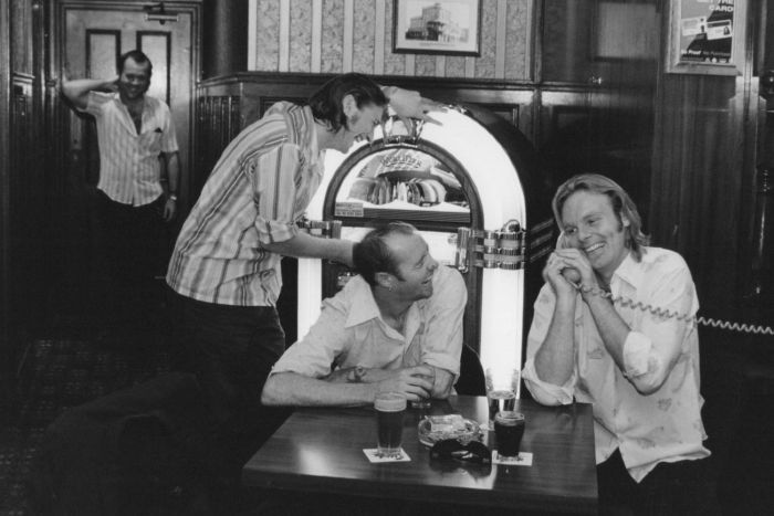 Four men sit around a juke box laughing, with one speaking on a phone