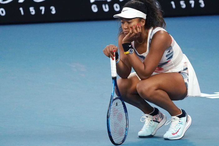 A tennis player stays on her haunches with her head propped in her hand.