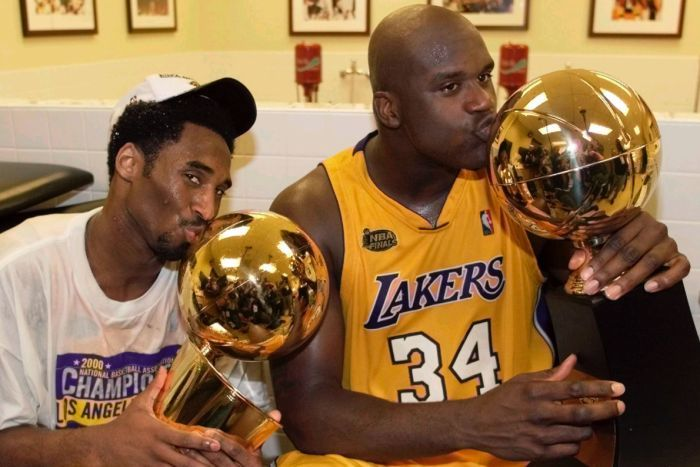 Kobe Bryant in a white shirt and cap next to Shaquille O'Neal in a Lakers jersey kissing NBA Championship trophies