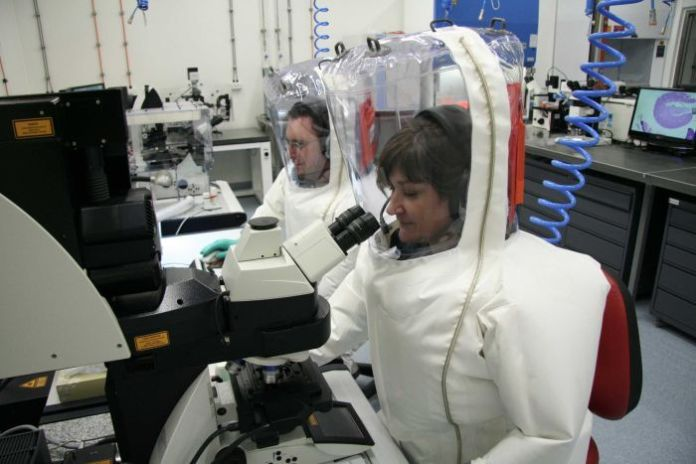 Two CSIRO scientists in full protective gear - one using a computer, the other using a microscope - at the Animal Health Laboratory.