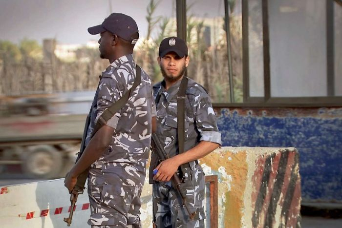 Two policemen holding guns stand at a checkpoint.