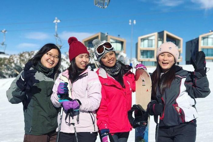 Maria Lukmanasari and three other women pose for a photo in a snowy area. They are holding skis and snowboards.