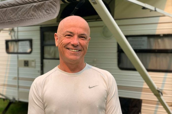 A bald man with a kind face smiling at the camera. He's standing in front of a caravan.
