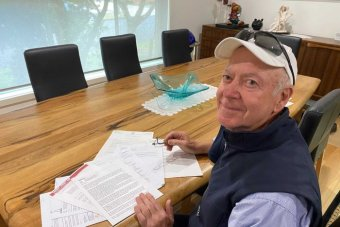An elderly man wearing a hat sitting at a table with some documents looking over his shoulder towards the camera