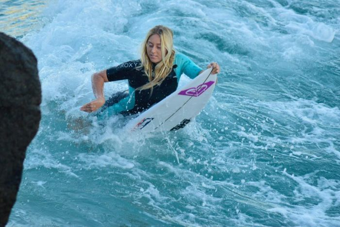 Alyssa Lock on her surf board in the water.