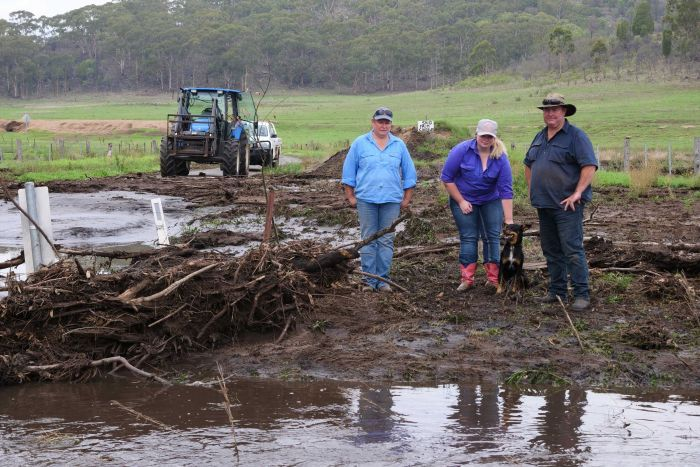 A man, woman and teenage daughter with a pet dog standing in mud on a farm with a blue tractor in the distance.